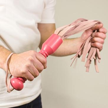 Růžové kožené důtky s dřevěnou rukojetí